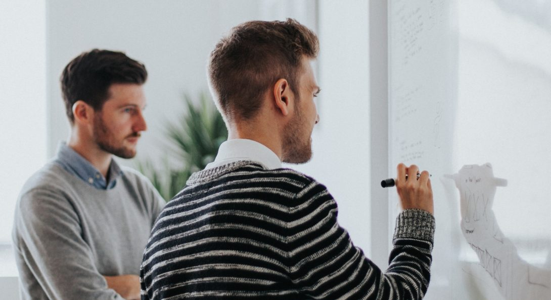 graduate students writing on a whiteboard
