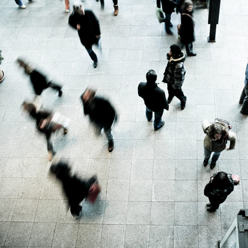 Abstract overhead view of people in an airport.
