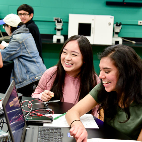 Female students smiling while coding