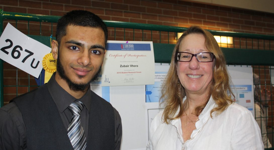 A student standing next to a faculty