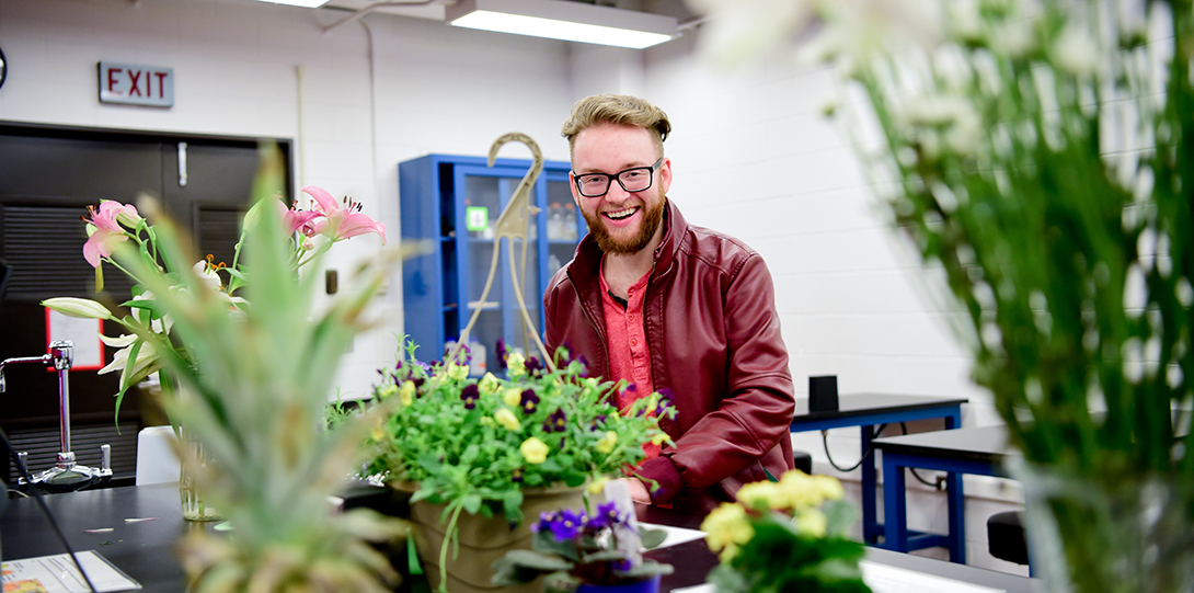 Student with plants in lab