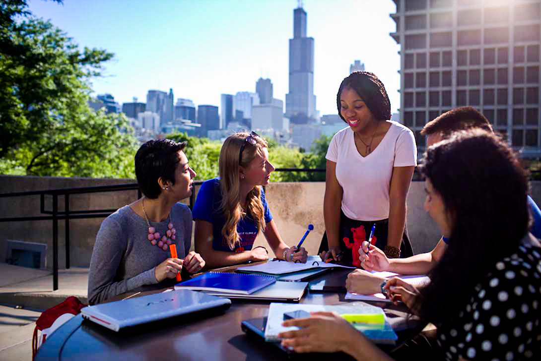 Students around a table with downtown Chicago in the background