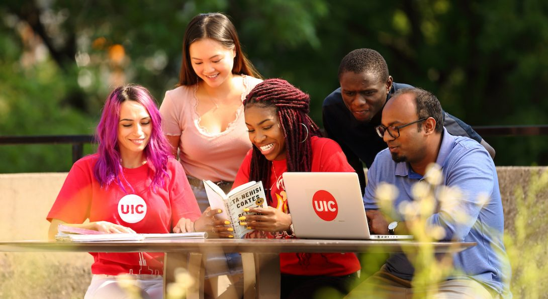 Diverse students at a laptop on campus grounds
